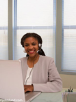 African american businesswoman wearing a headset and using a laptop and smiling. The woman is wearing a business suit and smiling at the camera. Large windows behind the executive.